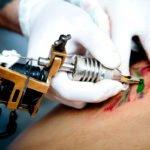 Tattoo artist making tattoo, toned image, focus on tattoo instrument